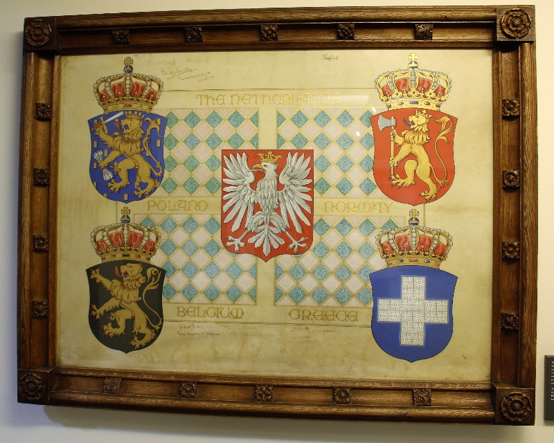 A framed scroll with pictures of coats of arms on it