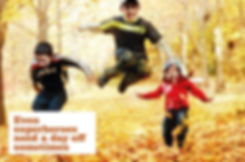 Superhero concept showing three yong children jumping in autumn leaves