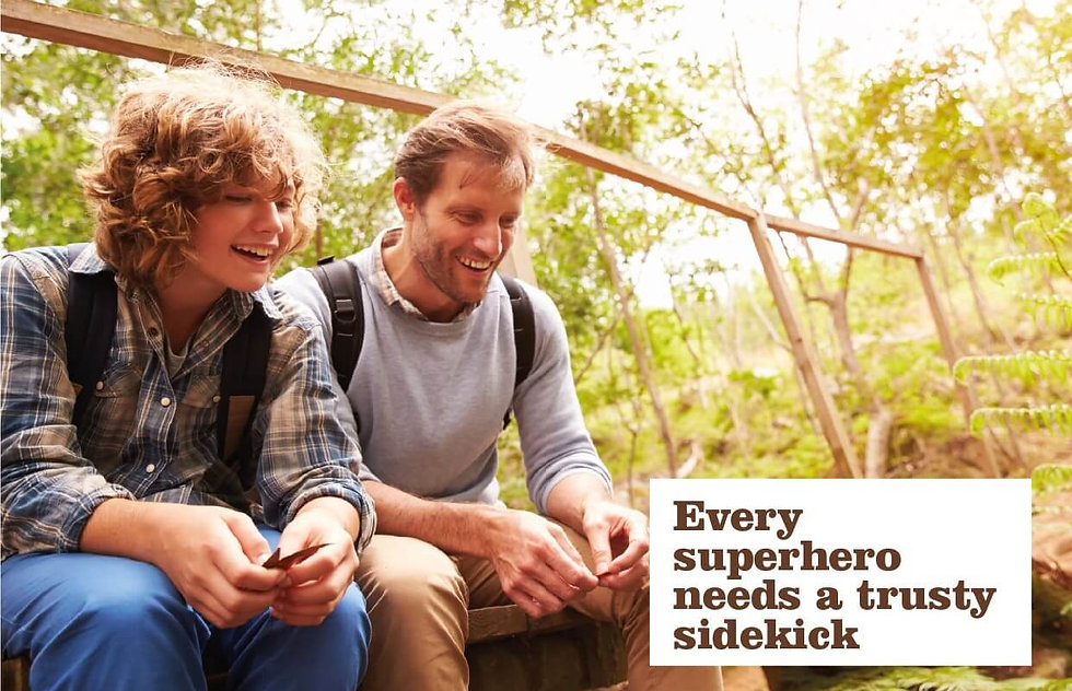 Superhero concept showing teenage boy and man sitting chatting outdoors