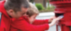 Dad and young boy posting letter inpostbox