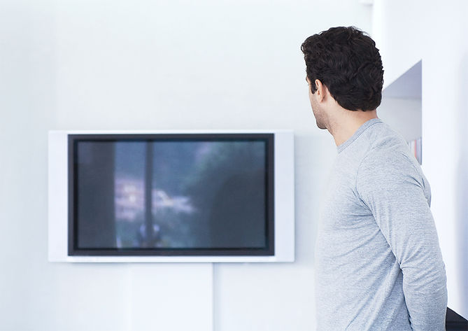 Stock image of man looking at a TV.