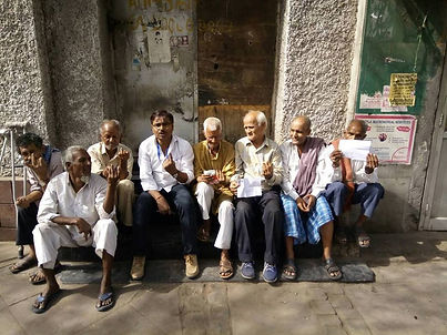 Sanjay Kumar sitting with seven homeless people showing voting ink on finger