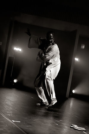 black and white photograph of a black man in African costume dancing on stage