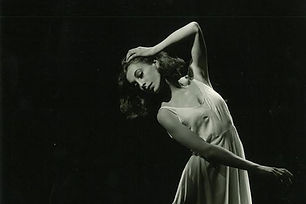 a black and white portrait of a caucasian woman dancing in a dress