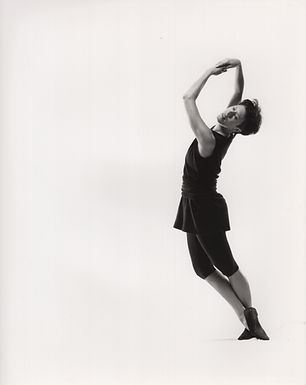 a caucasian woman dancing in a black costume with black jazz shoes