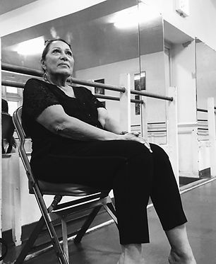 black and white portrait of woman in dance studio sitting in front of a mirror and barre
