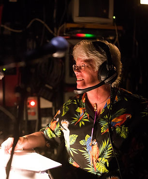 woman wearing a headset and a parrot shirt in front of a theater lightboard