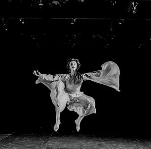 woman jumping in a theater wearing a flowy costume with long sleeves