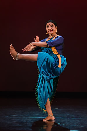 Indian woman in blue costume with one leg in the air performing bharata natyam dance