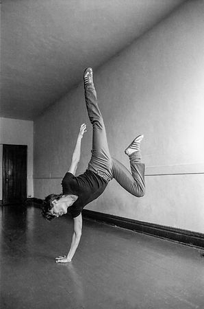 black and white photo of caucasian man doing a hand stand