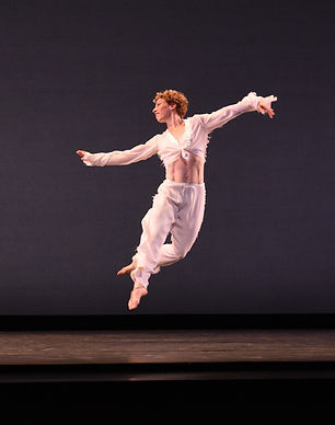 caucasian woman leaping in a white costume on an empty stage
