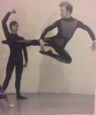 two men in unitards, one is leaping and the other is raising his fist