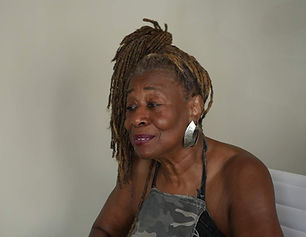 Black woman with dreadlocks and hoop earrings