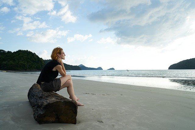 a woman sitting alone on a log on the beach looking our at the water