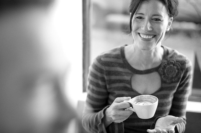 a woman smiling, holding a latte in a white coffee cup