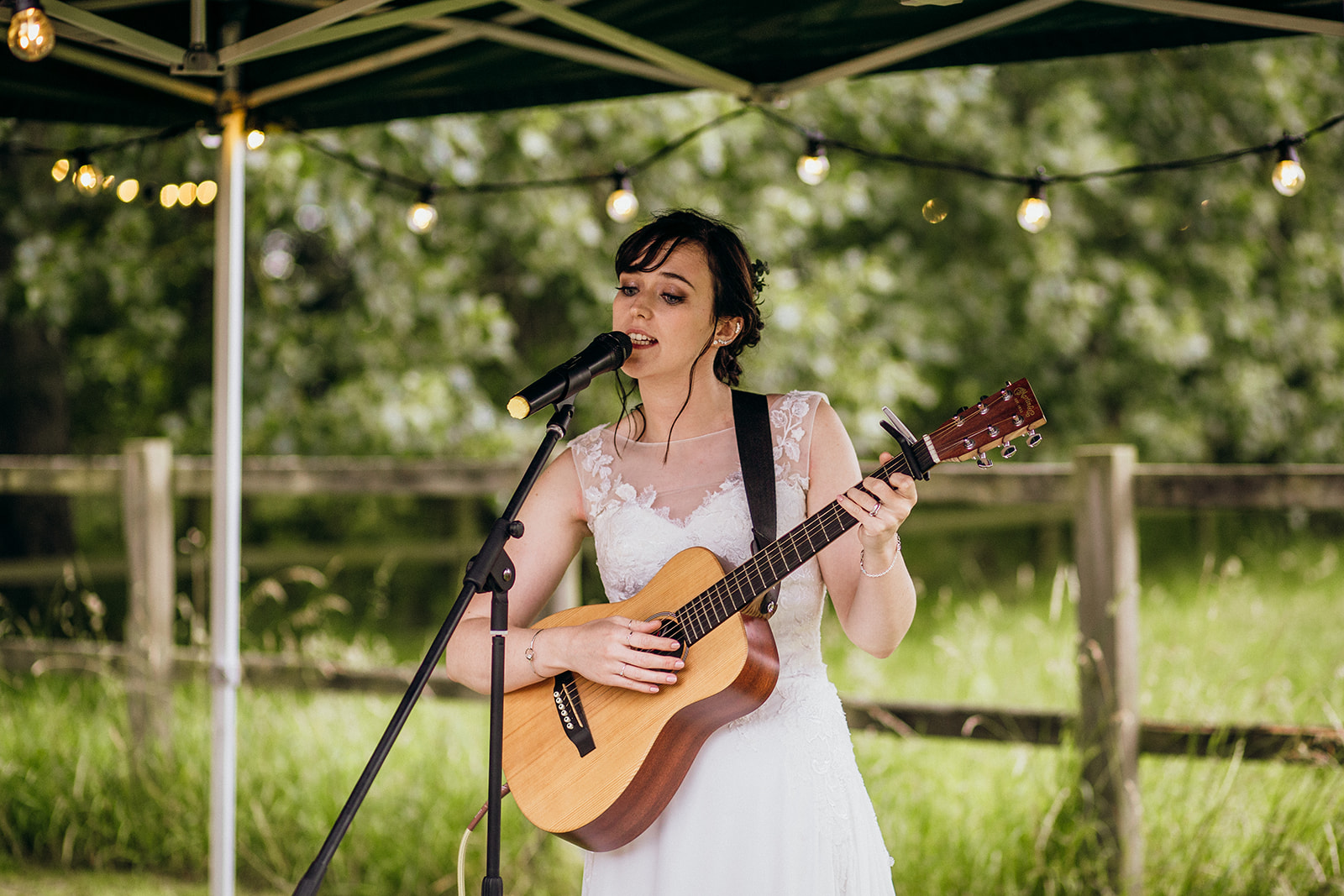 Bride playing guitar at wedding