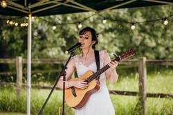 Bride playing guitar at wedding