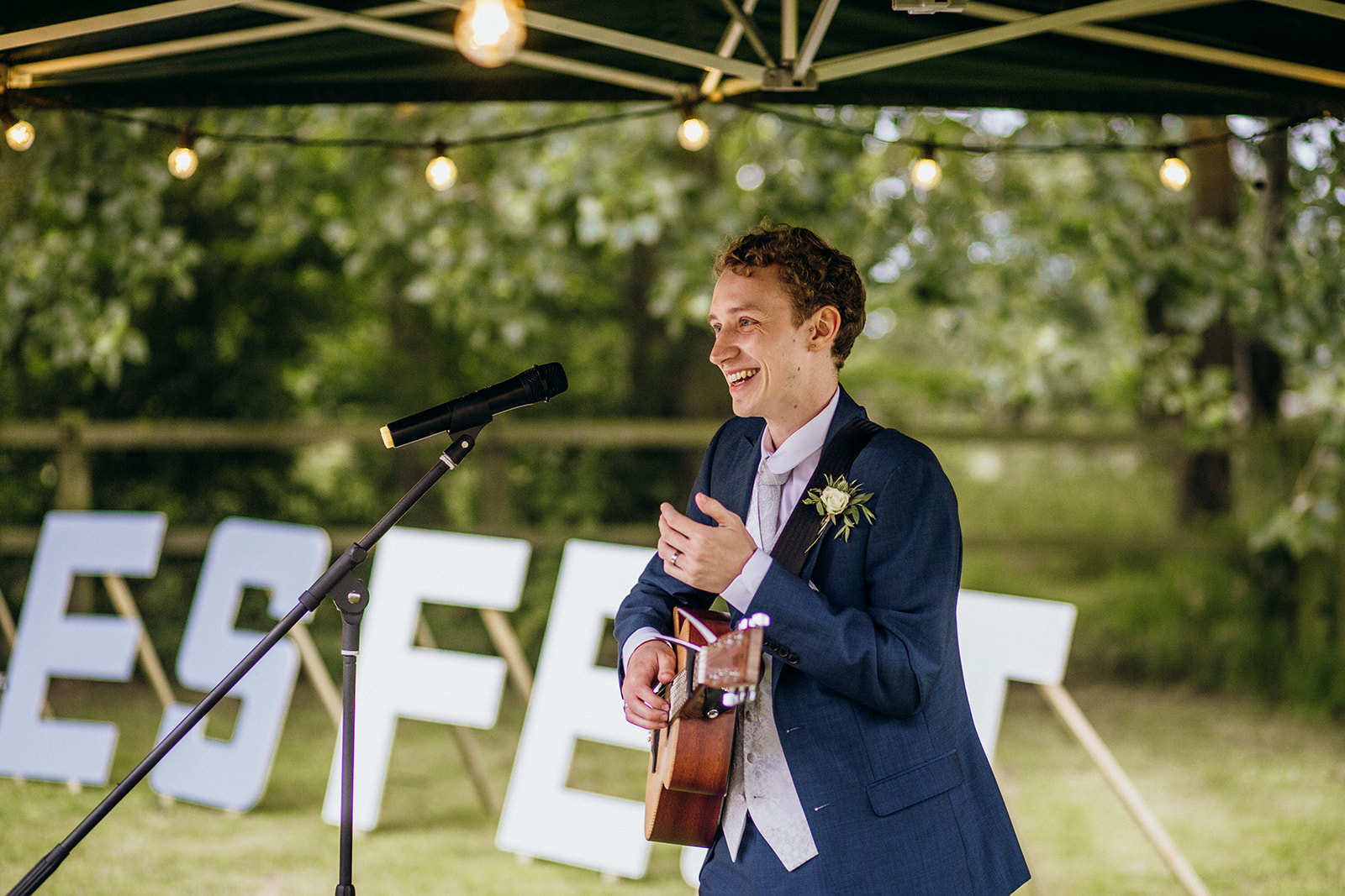 Groom playing guitar at wedding