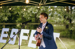 Groom playing guitar at wedding
