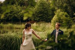 Bride and Groom walking by lakeside