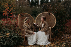 Brides sitting by lake