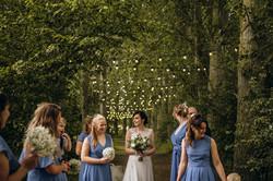 Bride and bridesmaids under walkway