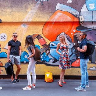 стена с граффити и полодые люди с рюкзаками