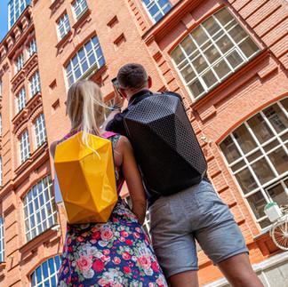 Молодая пара с рюкзаками делает фото на телефон на улице