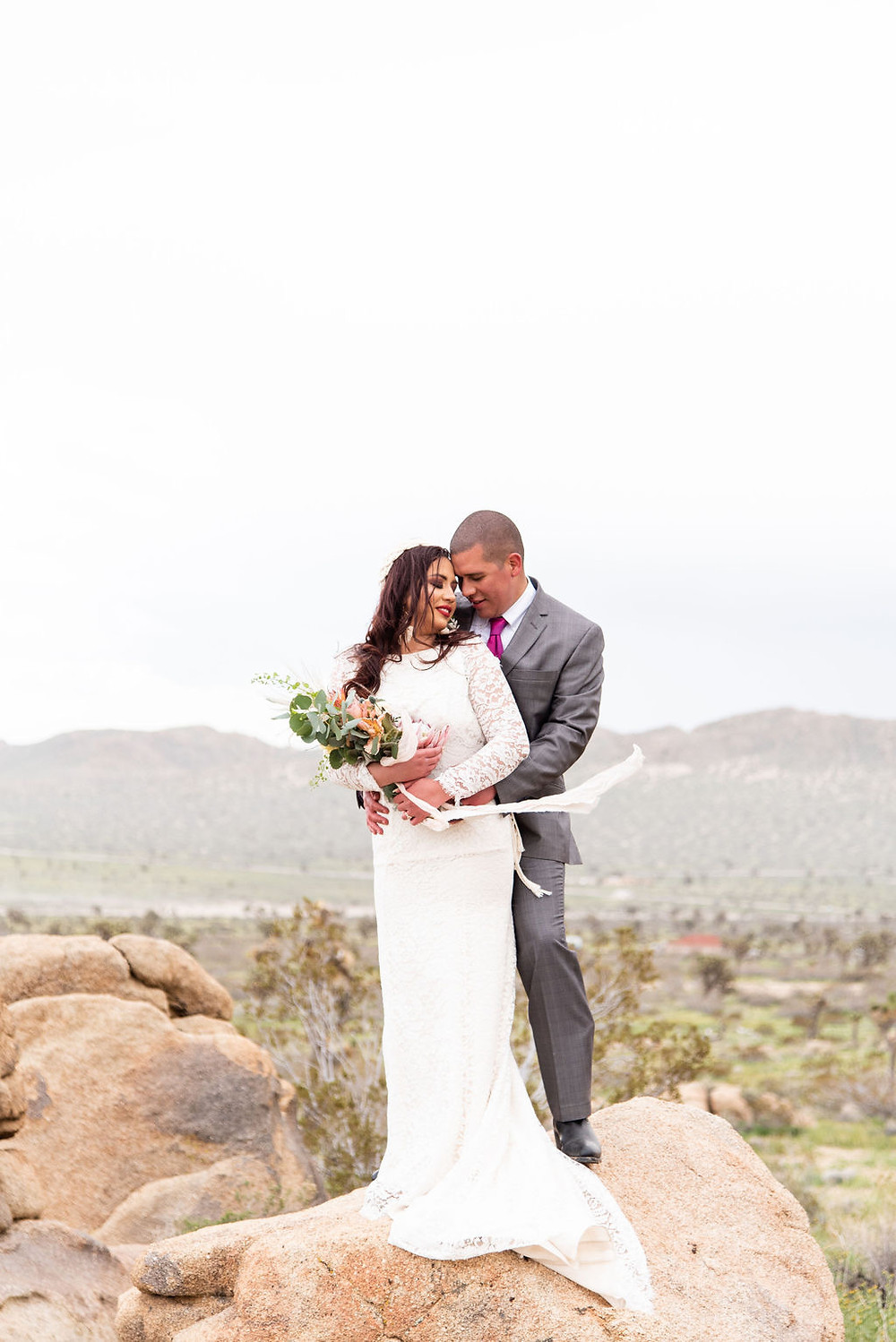 Bride and groom stand together on the Joshua Tree Rocks.