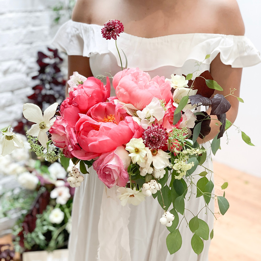 Wedding bouquet made with peonies, garden roses and butterfly ranunculus.