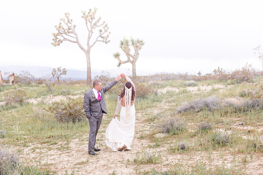 Boho bride wearing a macrome headpiece dance swith her groom under cloudy skies in Joshua Tree National park. The groom wears a boutonniere and smiles as he twirls his bride. #desertwedding #lacedress #bohobride #joshuatreewedding #macromeheadpiece #bohowedding