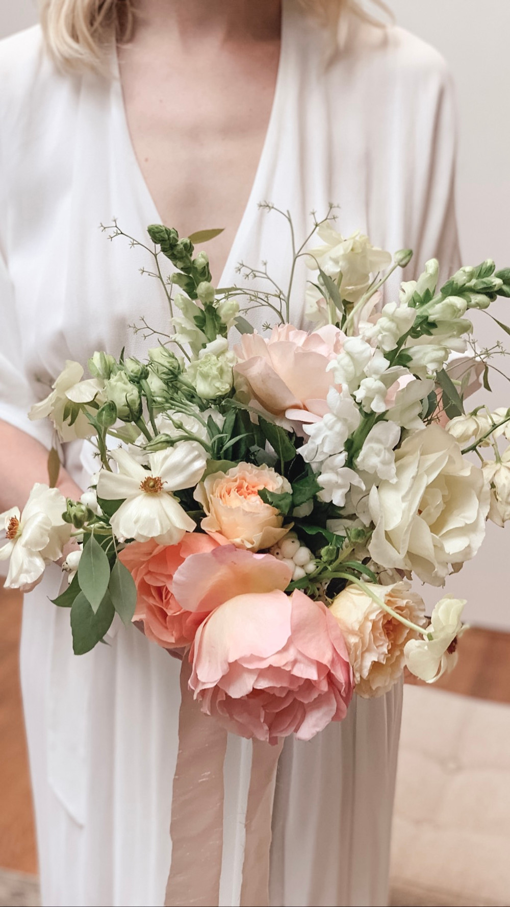 Wedding bouquet made with blush garden roses and soft greenery.