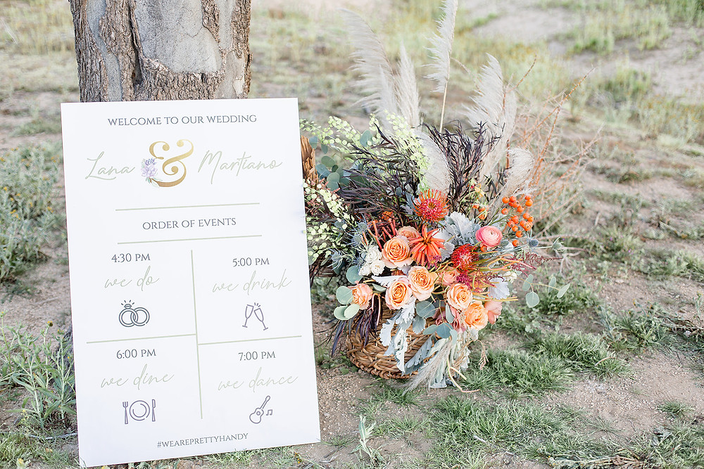 Coral an blush garden roses, pampas grass and lots of silver grieens and eucalyptus fill a boho style basket to greet Lana and Martiano's wedding guests. #weddingflowers #ceremonyflowers #bohobride #bohobasket #desertweddinginspiration #desertweddingdecor