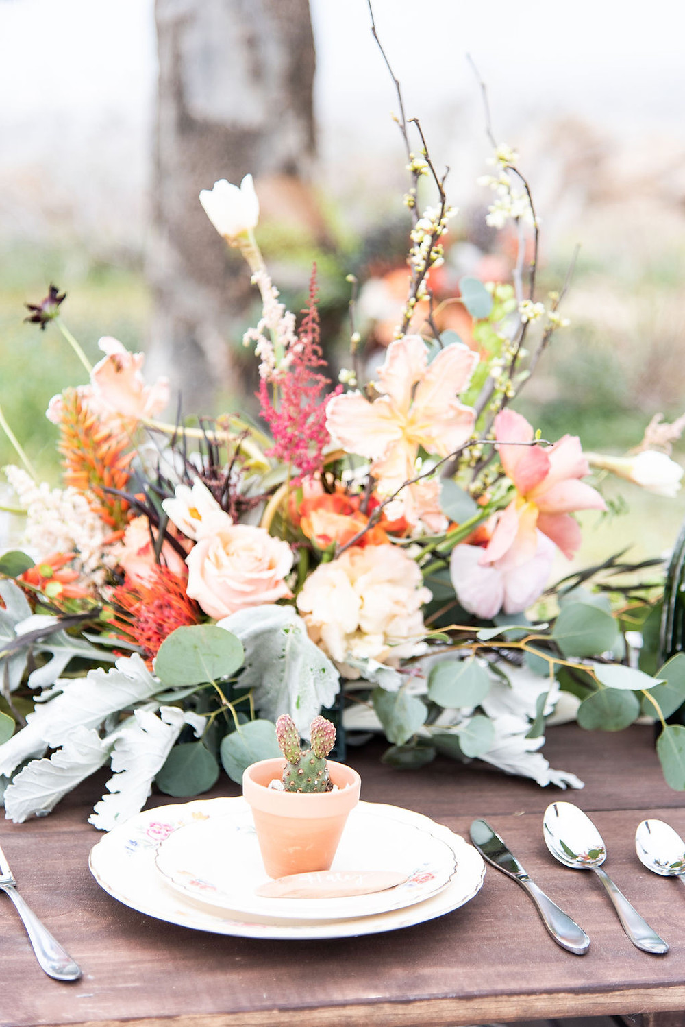 Beautiful rustic coarl colored floral arrangement on a desert tablescape.
