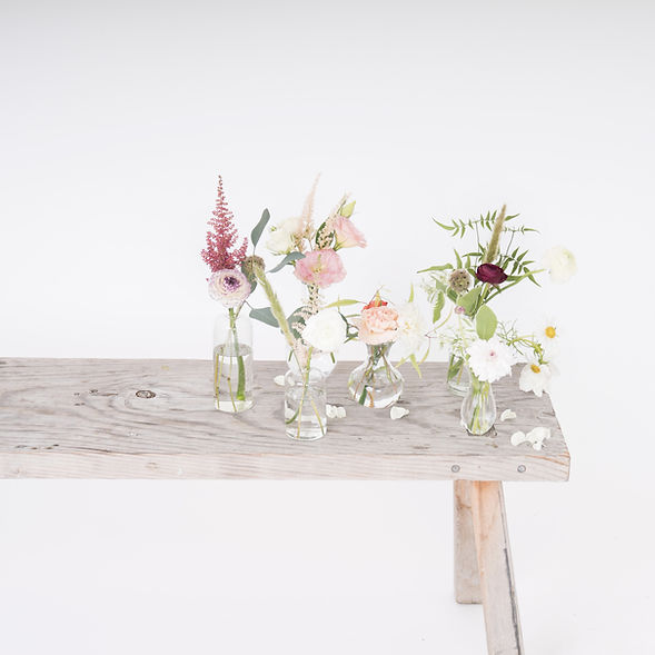 Glass bud vases fullof seasonal blooms and greenery, set on a rustic bench