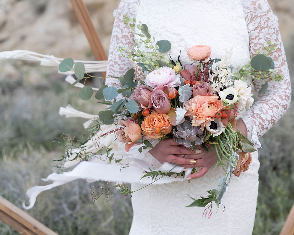 Wedding bouquet made with blush and coral colors, succulents and eucalyptus