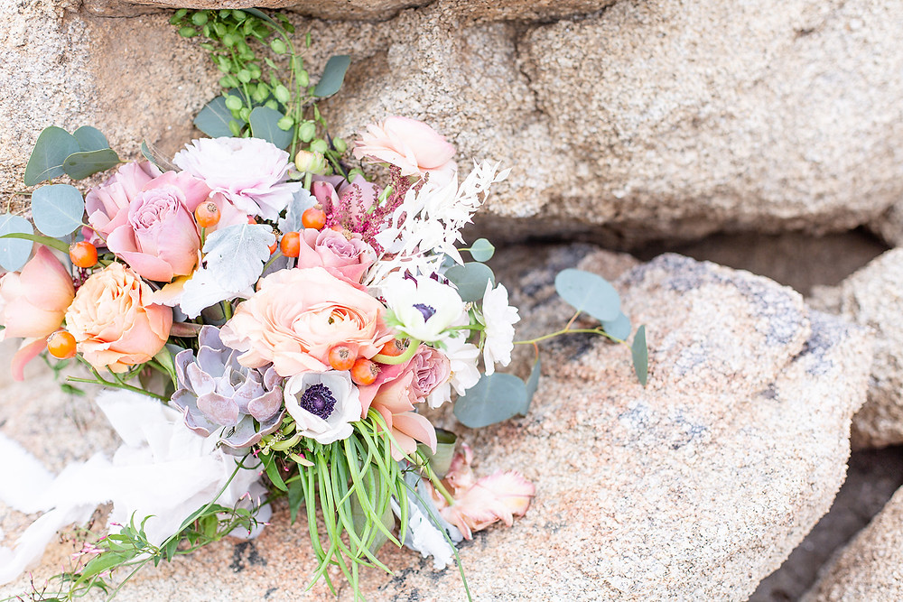 a boho wedding bouquet sits on the rocks of Joshua Tree. #bohobride #desertwedding #joshuatreewedding #succulentboquet #rusticwedding