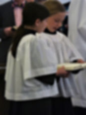 Some acolytes singing a hymn during Mass.