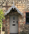 Wooden cottage door with traditional canopy