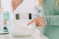 Closeup on hands mixing fluffy white royal icing in a glass bowl