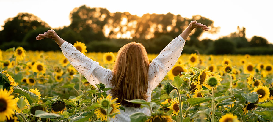 Wellness coach raising arms to the sunset in a field of sunflowers in Lancashire.