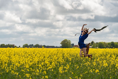 Wild Kind Photography owner and photographer, Kayleigh King jumping in Lancashire rapeseed fields.