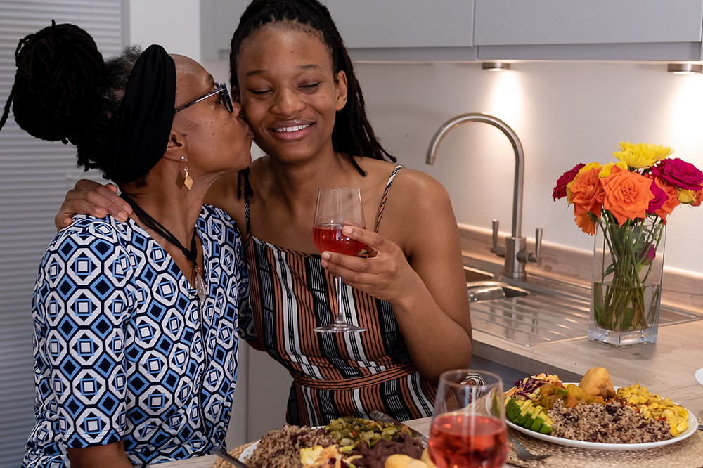Black mother kissing daughter on cheek in kitchen while enjoying vegan Jamaican meal they prepared together with wine.