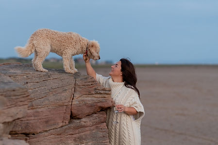 Liverpool nutritionist Rachel Philpotts and her labradoodle and a glass of prosecco at Red Rocks Beach in Liverpool following her full day brand photoshoot.