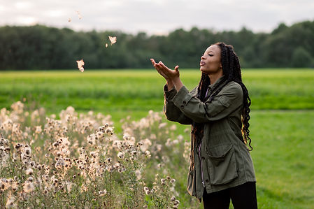 Liverpool herbalist, Tamiqua Williams blowing flowers in the wind at Mersey Forest after her sunset foraging brand photoshoot.