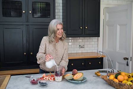 Lancashire homeopath and reiki master, Polly Tomlinson, making a breakfast smoothie in her kitchen during her brand shoot.