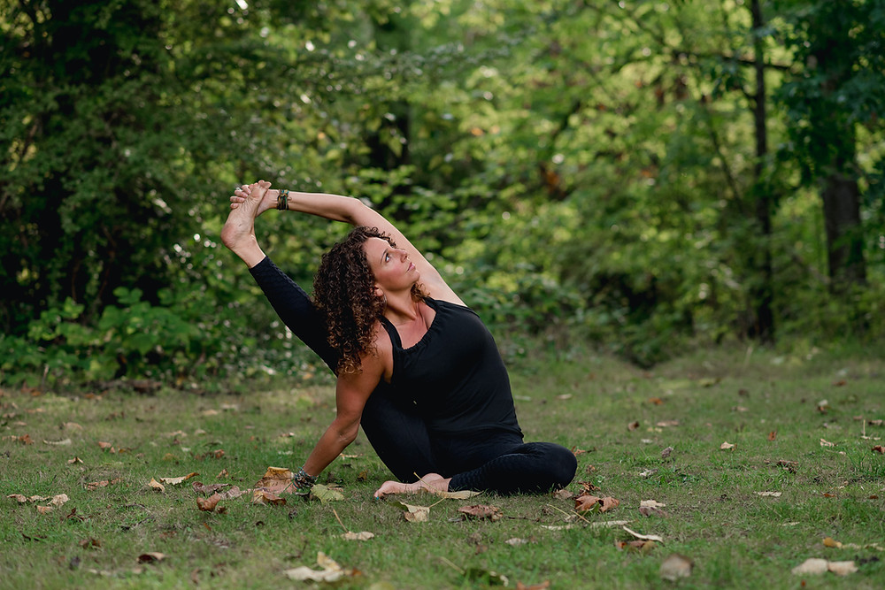 White women doing yoga in the forest, stretching leg up in compass pose.
