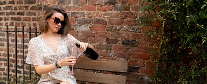 Young woman pouring prosecco during brand and content photoshoot at Liverpool airbnb.
