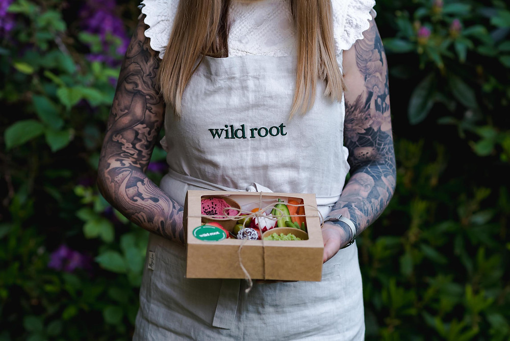Tattooed woman wearing apron, holding box full of fruits and vegetables. Shot from neck down.