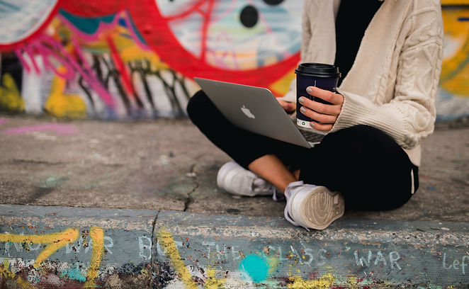 Woman on her apple laptop holding a cup of coffee at a skatepark in Liverpool covered in grafitti.